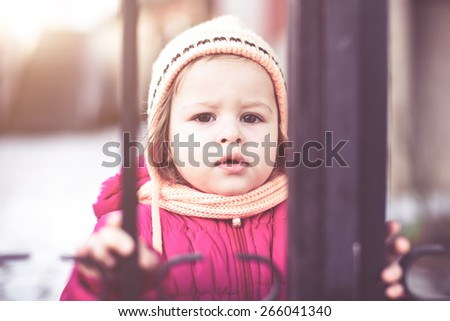 cute girl toddler standing in winter holding metal bars - stock photo