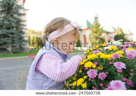 cute girl touching flower at flowerbed - stock photo