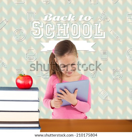 Cute girl using tablet against red apple on pile of books - stock photo