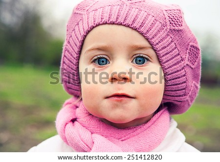 Cute girl walking in a meadow in spring day, close-up portrait, she is dressed in a purple beret - stock photo
