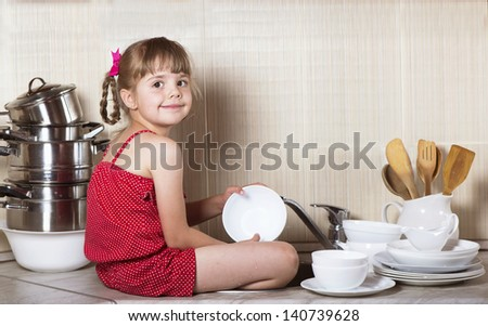 Cute girl washing the dishes - stock photo