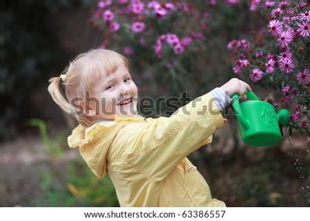 Cute girl watering flower in the garden - stock photo