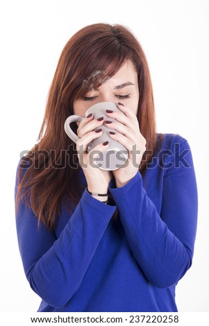 Cute girl wearing blue jersey smelling cup of coffee - stock photo