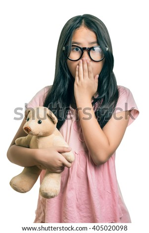 Cute girl  Wearing Eyeglasses, holding her dollm Showing Oops Expression at the Camera  isolated over white with clipping path - stock photo