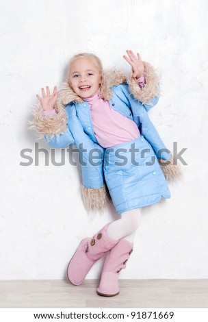 Cute girl wearing fashion blue winter coat and skirt - stock photo