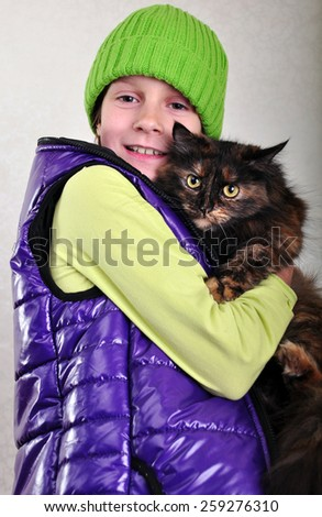 Cute  girl  wearing hat and warm vest with a cat - stock photo