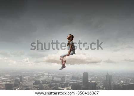 Cute girl wearing pajamas with toy bear in hand sitting on cloud