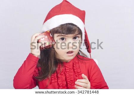 Cute girl wearing Santa hat holding a Christmas gift box - stock photo