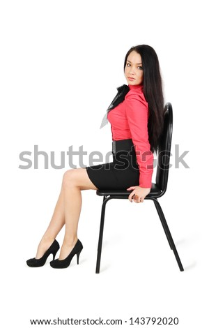cute girl wearing skirt and red shirt sits on chair isolated on white background
