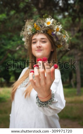 Cute girl wearing tradisional closes on wreath with raspberries on her fingers