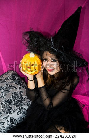 Cute girl wearing Witch costume holding an halloween pumpkin in her hand and smiling. Colorful indoor portrait celebrating Halloween. Trick or treat? Transparent dress, decorate pillow.