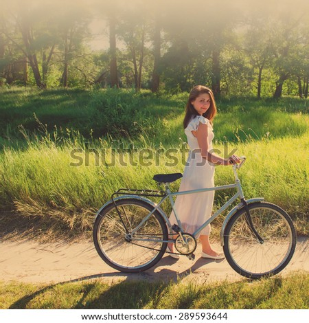 cute girl with a bicycle in a forest in the countryside - stock photo