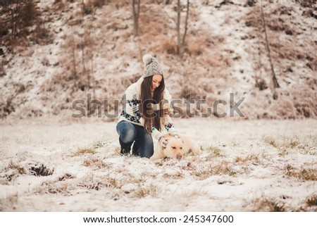 Cute girl with a dog playing in winter park - stock photo
