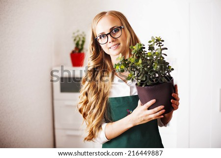 cute girl with a money Tree is at home gardener houseplants
