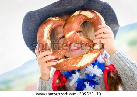 Cute girl with bavarian hat and big pretzel. Selective focus
