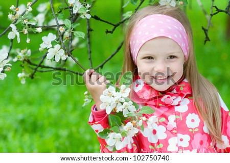 Cute girl with blossoming apple tree - stock photo