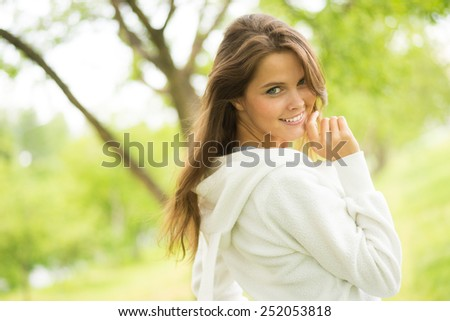 Cute girl with charming smile in summer park - stock photo
