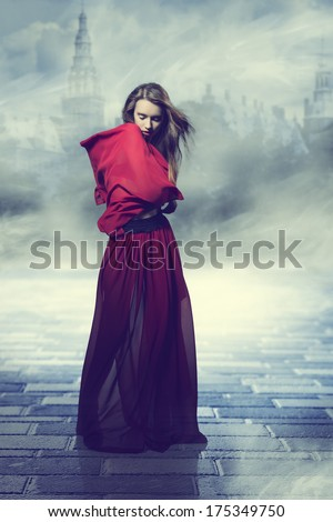 cute girl with creative fashion style and flying hair. Wearing long red fluttering skirt covering her shoulders