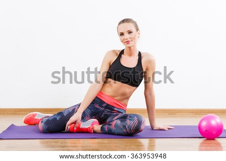 Cute girl with dark hair wearing snickers, dark leggings and black short top at gym, fitness, dumbbells, mat and ball on the floor, copy space.