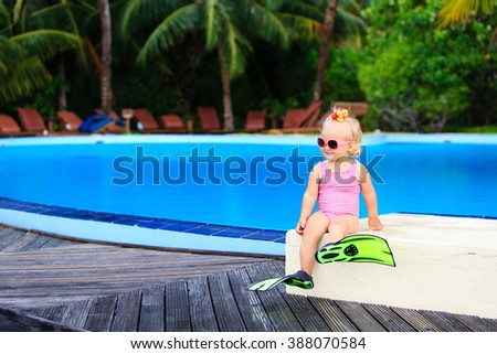 cute girl with flippers in swimming pool at beach - stock photo