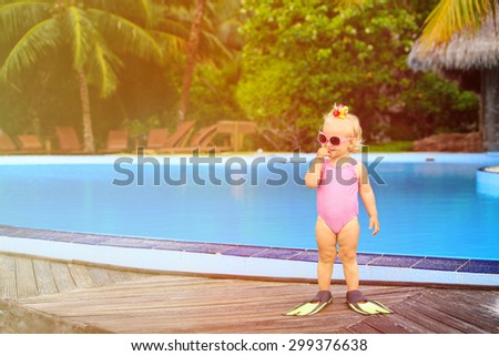 cute girl with flippers in swimming pool at tropical beach - stock photo