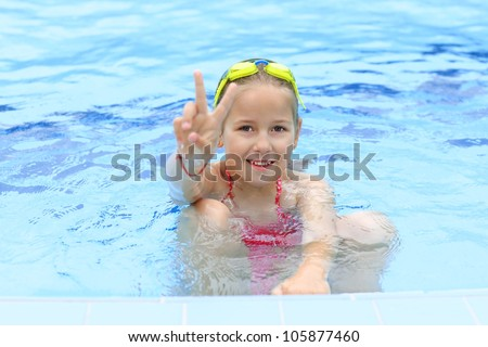 Cute girl with goggles in swimming pool showing victory sign - stock photo