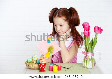 Cute girl  with greeting card and decorated Easter eggs, on light background