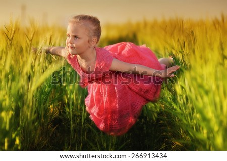 Cute girl with long hair flying in the meadow in spring day - stock photo