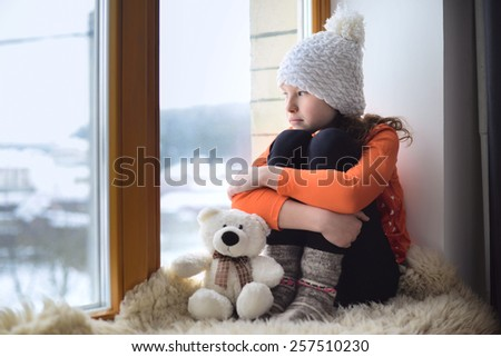 Cute girl with long hair sitting alone near window - stock photo
