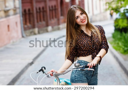 Cute girl with long hair wearing on blouse and shorts with bicycle smiling and standing on the street   - stock photo