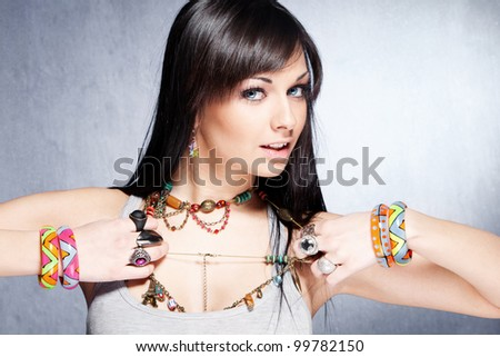 cute  girl with lot of necklaces, bracelets and rings studio shot - stock photo