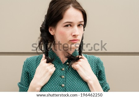 Cute girl with natural look wearing a green dress with white dots, making pigtails or ponytails with her hair - stock photo