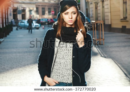 Cute girl with nude make up and black manicure wearing black coat and black scarf, wearing headphones, copy space.