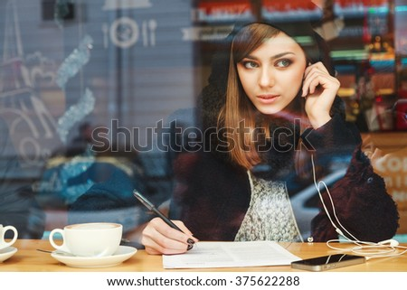 Cute girl with nude make up and brown hair wearing black coat and black scarf, writing in notebook and sitting with cup of coffee and headphones behind window. - stock photo
