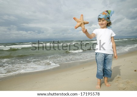 Cute girl with starfish on the beach