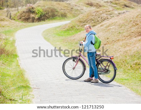 Cute girl with the bike in the park on a spring day - stock photo