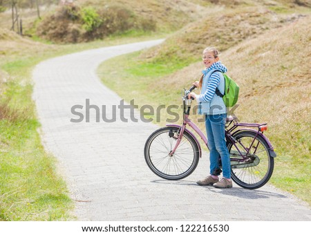 Cute girl with the bike in the park on a spring day