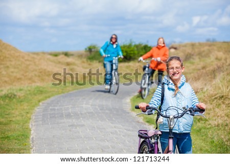 Cute girl with the bike with her mother and grandmother in the park on a spring day - stock photo