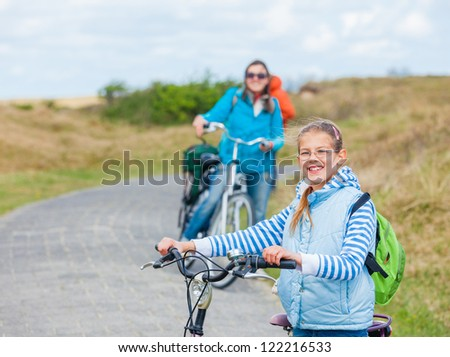 Cute girl with the bike with her mother and grandmother in the park on a spring day