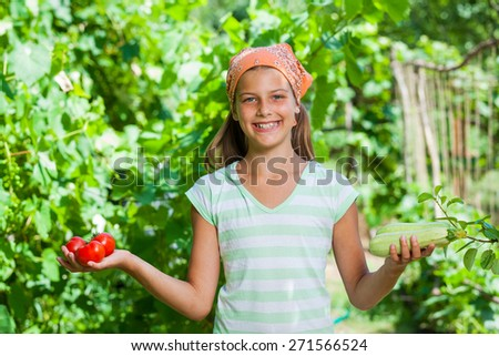 Cute girl with vegetables in summer garden