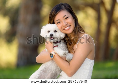 Cute girl with white dog smiling and hugging at the park outdoors - stock photo
