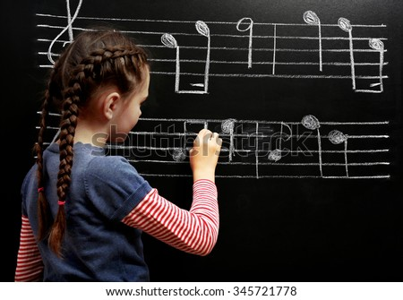 Cute girl writing at the blackboard with musical notes, in the classroom - stock photo