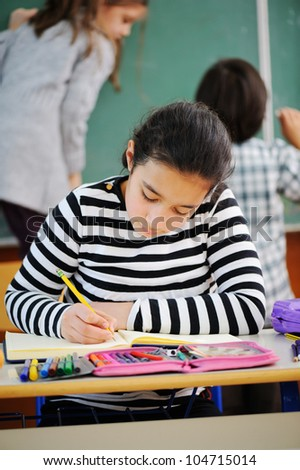 Cute girl writing in school classroom - stock photo