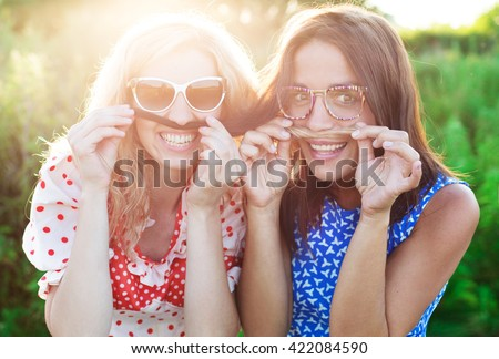 cute girlfriend in glasses makes selfie photo Two happy beautiful women making selfie photo with mobile phone - stock photo