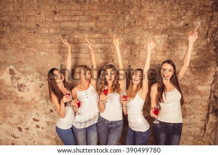 Cute girls celebrating hen-party with raised hands and stemware