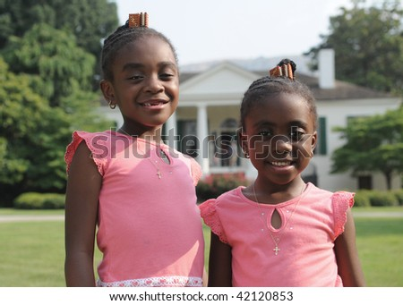 cute girls dressed in pink in front of stately southern mansion