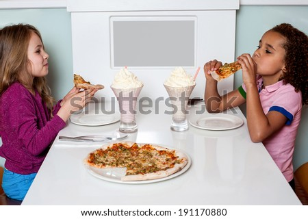 Cute girls eating pizza together in a restaurant - stock photo