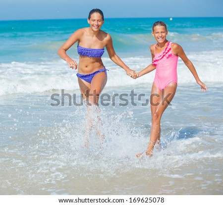 Cute girls friends running together in the beach shore on summer vacation