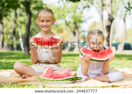 Cute girls in park eating juicy watermelon