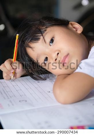 Cute girls is doing her homework. - stock photo